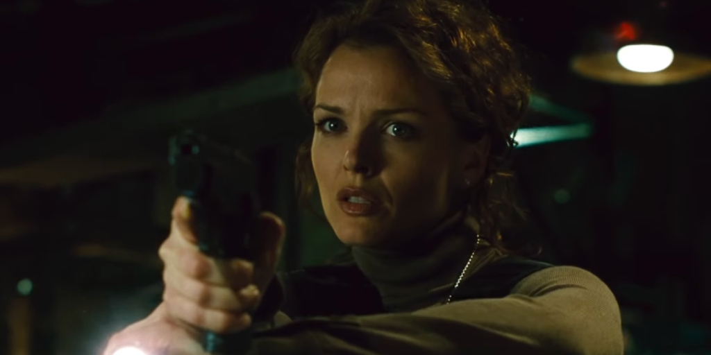 Allison Kerry holds a gun in Saw 2.